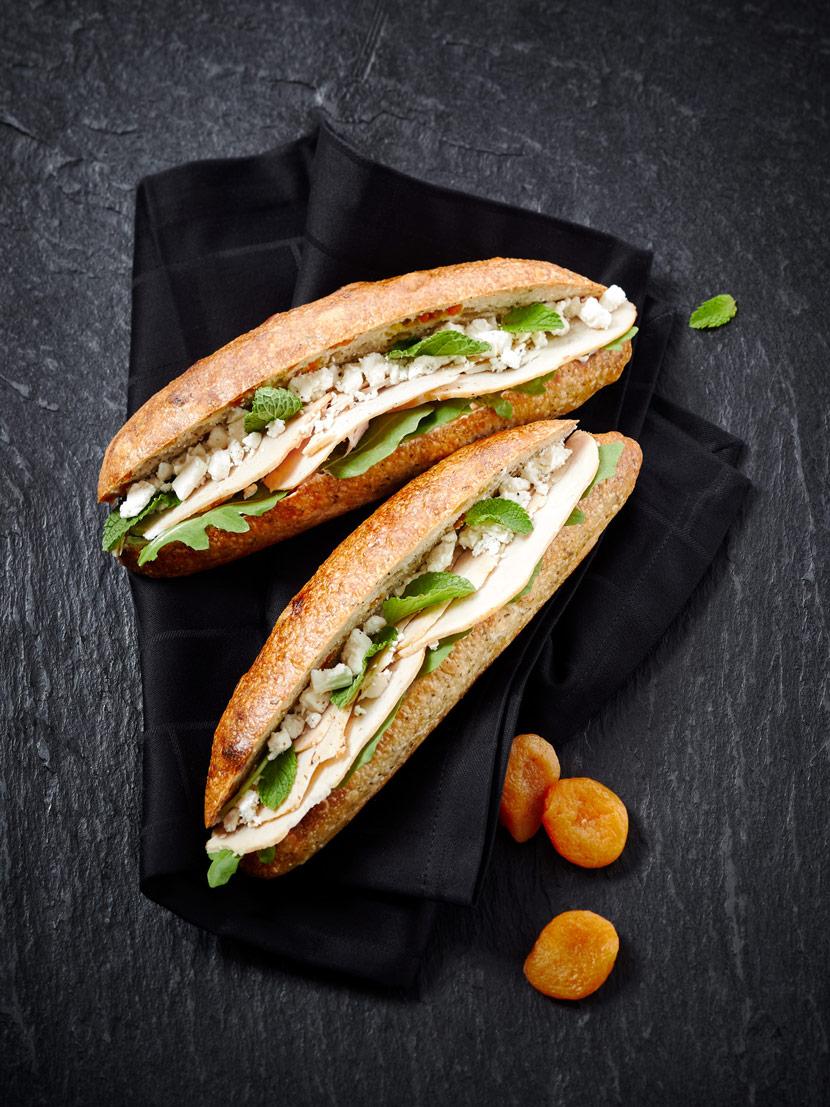 Sandwich garni de poulet, fromage crémeux, féta, roquette et menthe fraîche ; Sandwich du mois de juin 2019.